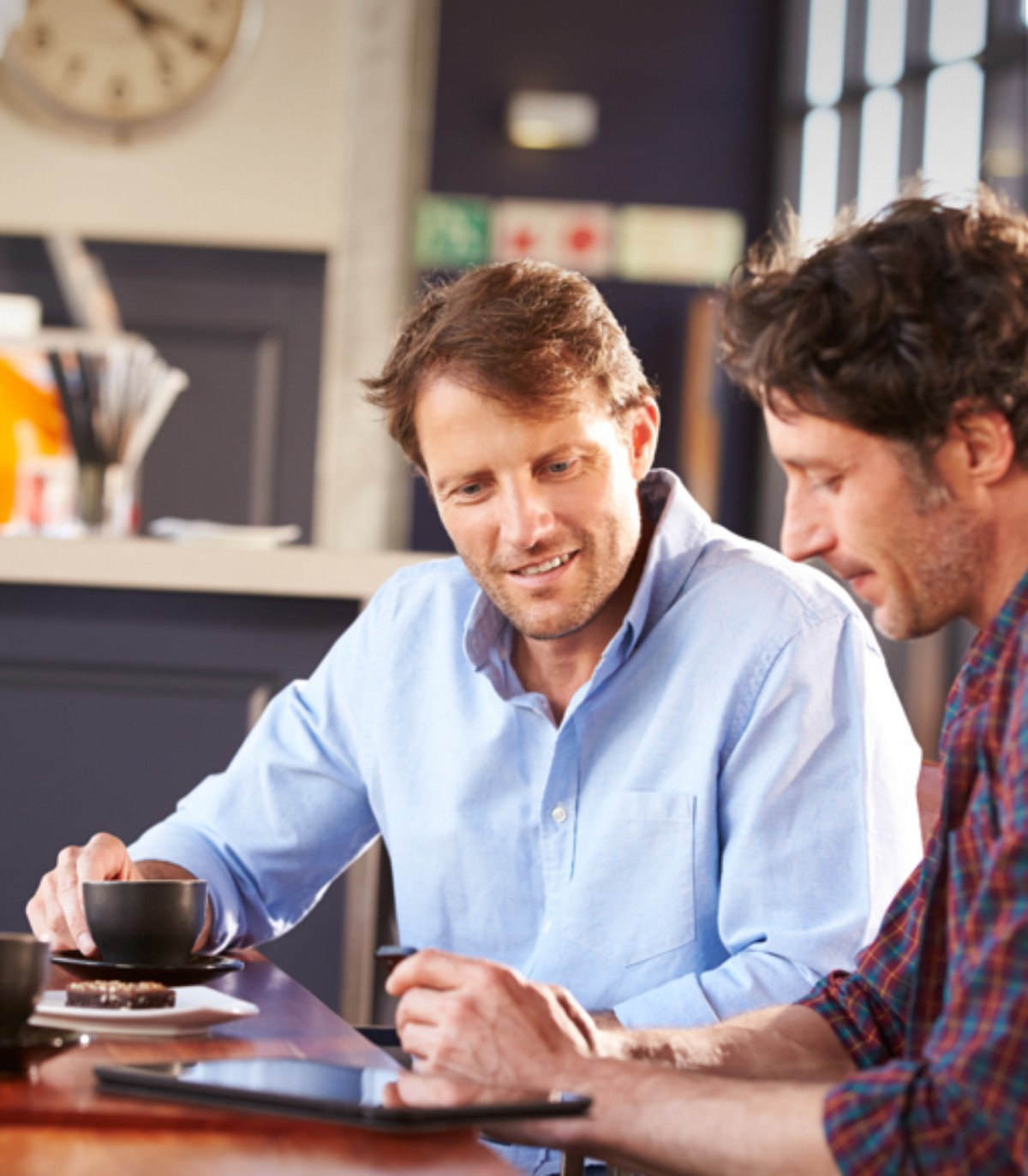 Two men working together in a coffee shop