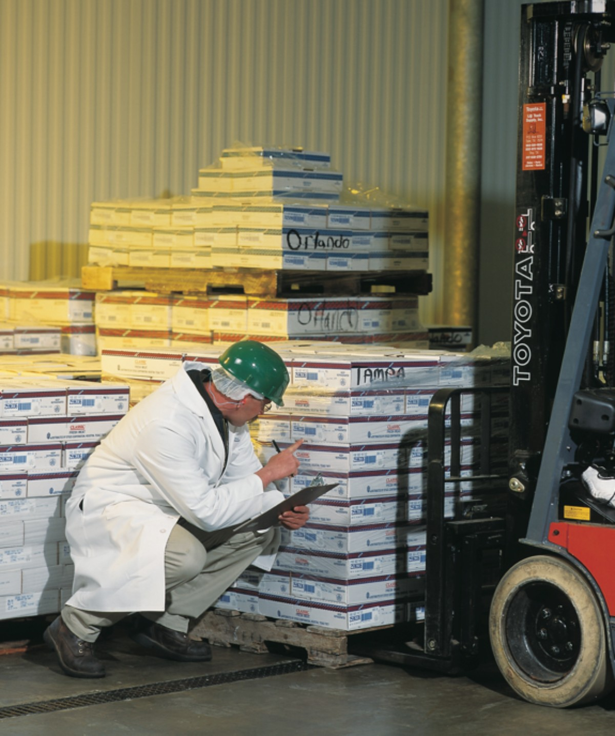 Man inspecting pallets in a warehouse